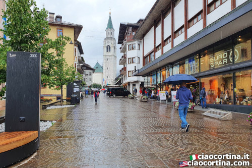 People in front of the Cooperative of Cortina on a rainy day